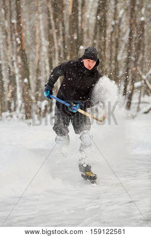 Hockey player runs throwing up puck and snow at outdoor skating rink in park.
