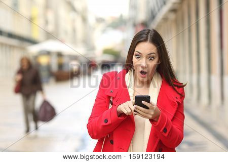 Front view of a fashion amazed woman checking smart phone in the street and walking towards camera