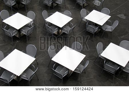 Several tables and chairs, arranged neatly for visitors to come sit for a meal, seen and photographed from above.