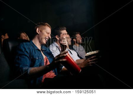 Young man with friends in cinema hall watching movie and laughing. Group of people watching movie in theater.