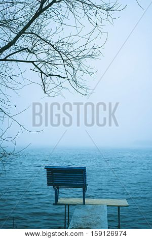 Lonely Bench Overlooking A Winter Lake Or Sea