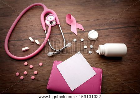 Pink stethoscope and pills on wooden background. Breast cancer concept