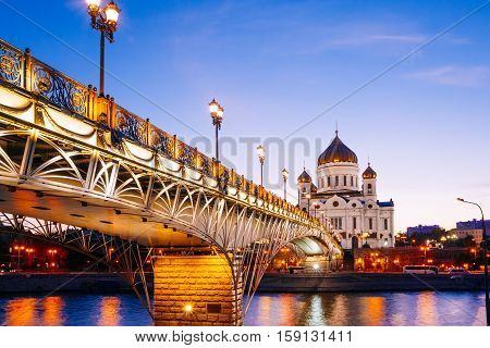 Beautiful view of the Christ the Saviour Cathedral in the blue hour. Pedestrian Patriarchal bridge with illumination. Night