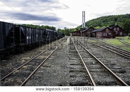tracks running though old railroad yard next to rusting coal hoppers and maintenance shop with twin smoke stacks