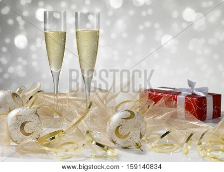 Two champagne glasses golden decoration. Red gift with white ribbon stylish tinted