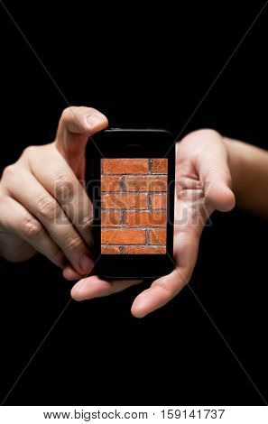 Hands Holding Smartphone showing Red Brick Wall (on black background with very shallow depth of field)