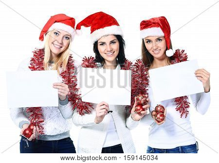 three young women with blank cards in suits of Santa Claus.the photo has a empty space for your text.