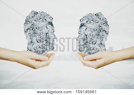 Hands holding abstract lung shaped gears on light city background. Industry concept