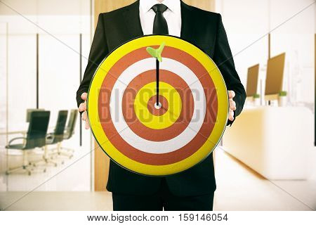 Businessperson holding dartboard with arrow in the middle. Modern interior background. Aiming concept. 3D Rendering