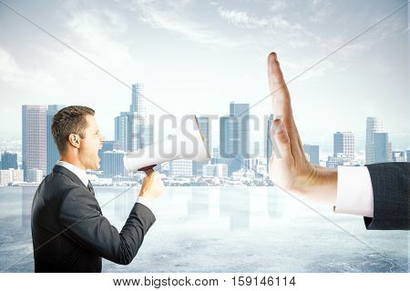 Angry caucasian businessman with megaphone screaming at hand showing stop gesture on city background. Protest concept