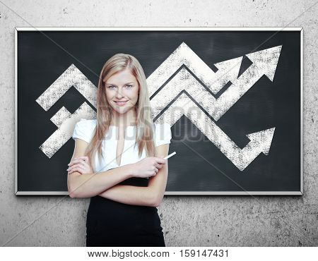 Attractive young businesswoman with chart arrows on blackboard. Financial growth concept