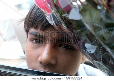 DELHI, INDIA - FEBRUARY 13 : A poor boy trying to sell flowers on the street of Delhi, India on February 13, 2016.