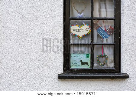 Cute Cottage Black Window With Decorative Signs On White Painted Cottage Wall