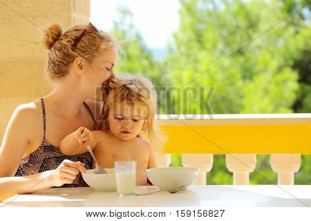 Young pretty happy mother woman and baby son boy child sit at table on balcony eating from plates and drinking milk from glass outdoor on green natural background
