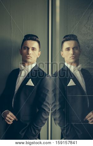 Man in suit with white bow tie handkerchief young elegant stylish turns sideway with hand in pocket and reflects in mirror on grey background