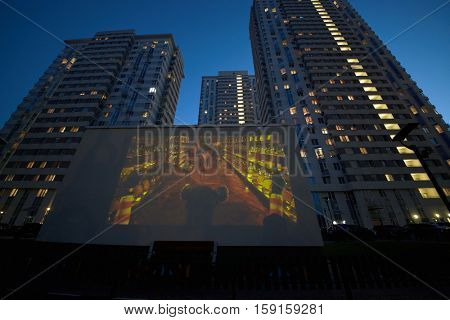 MOSCOW, RUSSIA - MAY 25, 2016: Translaion of children cartoons onto the big screen from notebook in the yard of a residential complex of Elk Island.