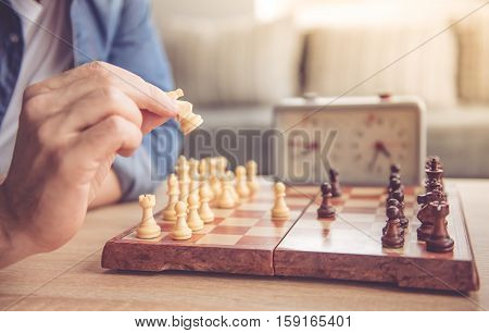 Cropped image of young man holding a chess piece while playing chess