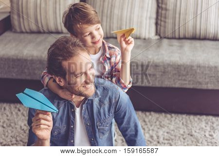 Father and son are playing with paper planes and smiling while spending time together at home