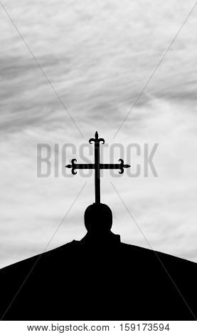 Holy cross silhouette against cloudy sky (B/W)