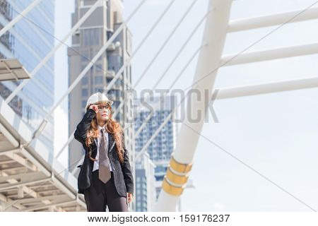 Middle-aged Engineer or architect woman wearing construction hard hat or helmet looking up. Middle-aged women professional standing in central of city.