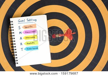 smart goals setting and hand written acronyms definition on the notebook with red arrow dart target hitting in bullseye on dartboard Business success concept