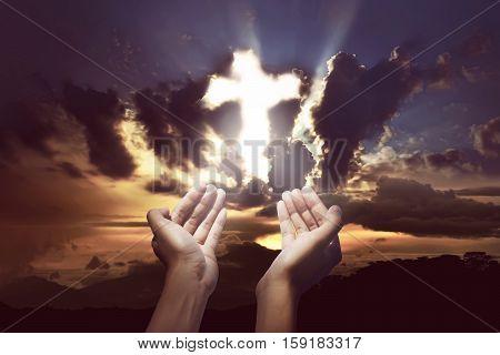 Human Hands Praying Over The Cross
