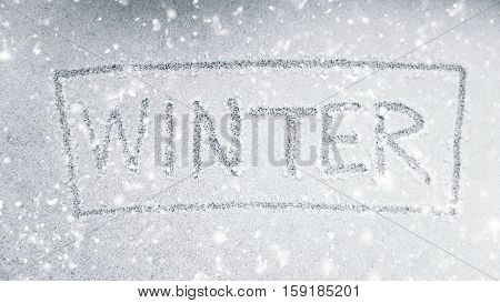 Handwriting winter word on light snow with snow falling effect