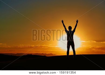 Silhouette of a man with his hands up during the sunset in Erg Chebby Merzouga Sahara desert situated in Morocco Africa