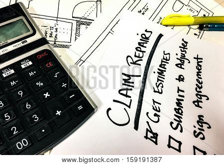 Making a Home Insurance Claim papers and estimates on desk with calculator and handwritten Claims checklist for adjuster in major home insurance loss with words written on pad next to blueprints and estimates
