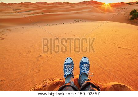 Feet of a woman relaxing on sand dunes and looking at sunrise in Sahara Desert Merzouga Morocco