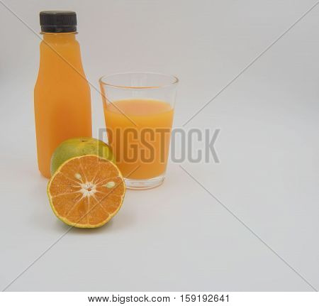 Fresh orange  fruit and  juice in a bottle and glass on white background.