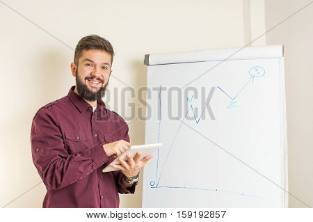Young bearded man presenting by the flipchart
