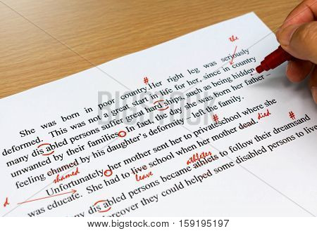 english proofreading sheet with hand holding red pen
