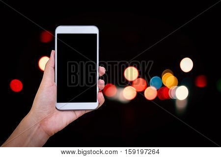 Hand hold and touch screen smart phone on on abstract bokeh of city night light background.