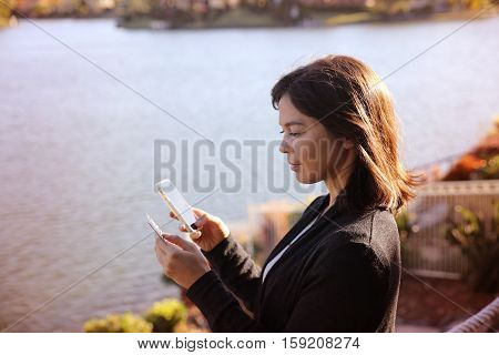 Woman Holding Credit Card And Mobile By The Lake, Online Shopping, Internet Banking Concept,toning