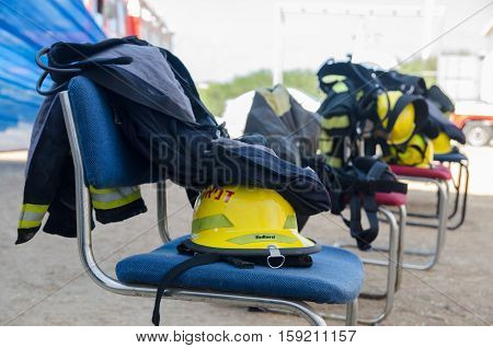 RISHON LEZION, ISRAEL - APRIL 10, 2013: firefighter equipment - suits and helmets, stacked on a chair