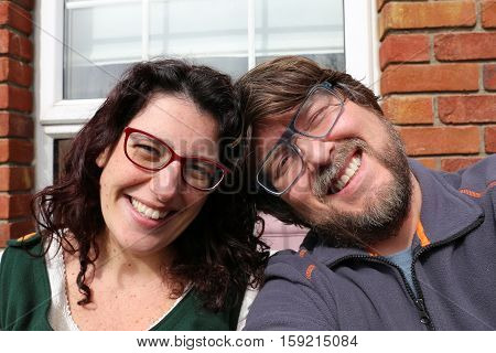 Selfie of a young happy couple in front of their home smiling sitting close together