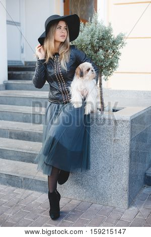 Beautiful woman with long blonde straight hair and grey eyes wearing a black hat with a large brim,a black leather jacket and long blue skirt,posing in the city with his friend,the dog breed Shih Tzu,the lady with the dog,walking outdoors in autumn