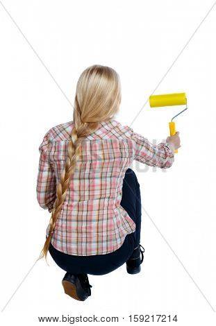 Back view of a girl who paints the paint roller. rear view people collection. backside view of person. Isolated over white background. girl smears the wall Yellow roller.