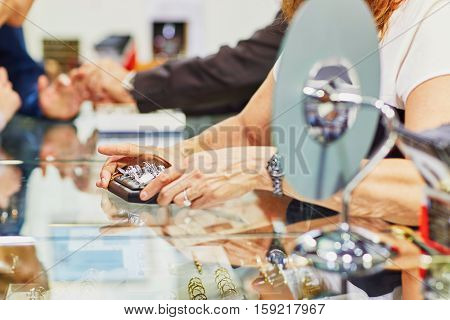 Jeweler Helping Client To Choose Wedding Ring