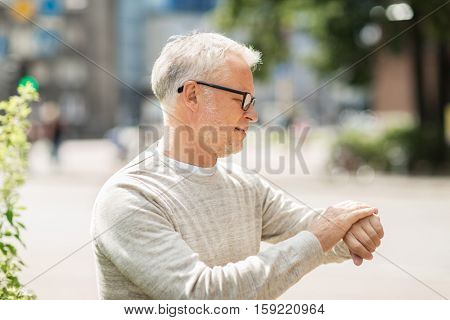 punctuality and people concept - senior man checking time on wristwatch or smart watch on his hand in city