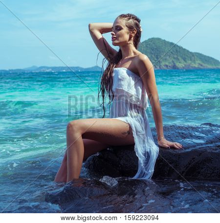 Sensual brunette woman in white dress with wet hair having closed eyes and sitting on the rock over beautiful sea and tropical island background