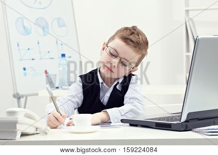 Little business boy working at the table