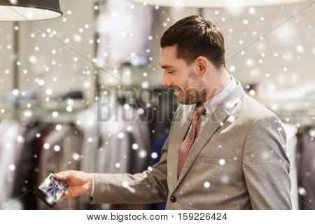 sale, shopping, fashion, style and people concept - elegant young man in suit choosing bow-tie in mall or clothing store over snow