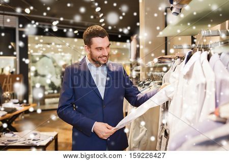 sale, shopping, fashion, style and people concept - happy young man in suit choosing shirt in mall or clothing store over snow