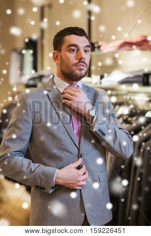 sale, shopping, fashion, business style and people concept - elegant young man choosing and trying on suit and tie in mall or clothing store over snow