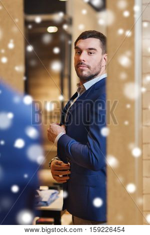 sale, shopping, fashion, style and people concept - elegant young man choosing and trying jacket on and looking to mirror in mall or clothing store over snow