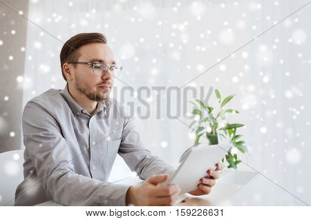 business, startup and people concept - businessman or creative male worker with tablet pc computer at home office over snow