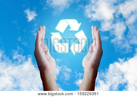 Asian young hand holding recycle icon and nature clouds and sky background.