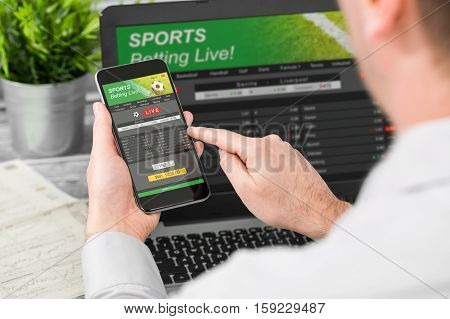 betting bet sport phone gamble laptop over shoulder soccer live home website concept - stock image